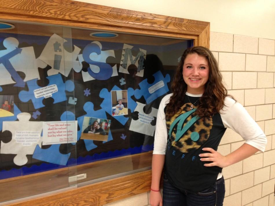 Junior Rachel Harris poses beside the display case outside of the high school main office.  Harris created the display, which is devoted to promoting autism awareness.