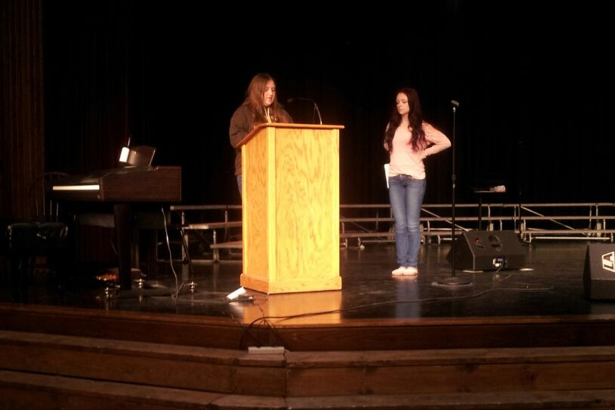 Angela Wheeler, the 2014 Valedictorian, practices at the podium in the high school auditorium, while Salutatorian Miranda Lowery waits her turn.  The two will deliver their addresses to the Class of 2014 at Commencement on June 5.
