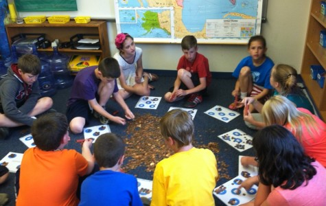 """Fourth grade students from Tommie Murray's class work together to count the change collected at the elementary school for their project  """"Change Changes South Sudan."""