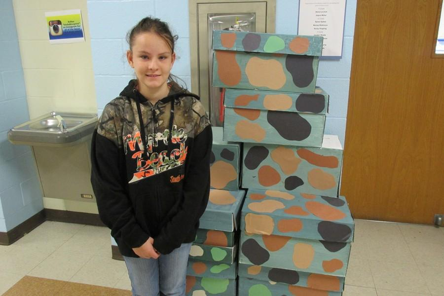 Middle schooler Paige Otto poses with supplies gathered for the SOS for Troops project.