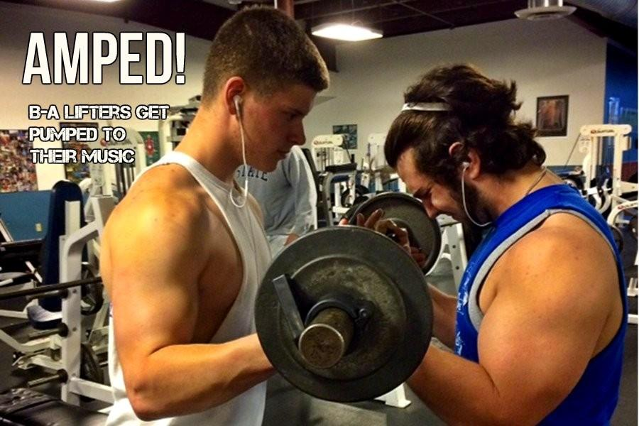 Tyson Miller and Tyler Shultz listen to their workout music as Shultz goes for max reps.