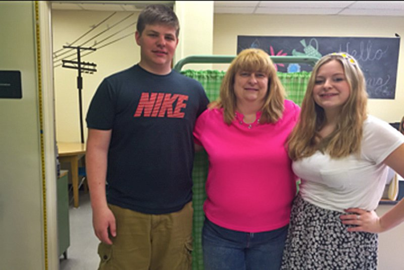 School nurse Kelly Hoover flanked by sophomore Jacob and junior Emily.