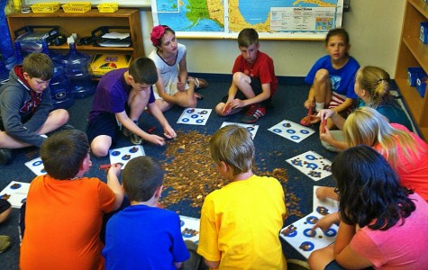 Students in Ms. Murray's class count pennies to be donated to a project that provides water wells in South Sudan.