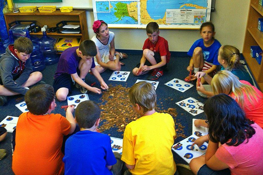 Students in Ms. Murrays class count pennies to be donated to a project that provides water wells in South Sudan.
