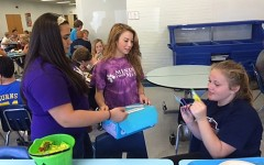 Freshmen Aedium members Paige Wenner and Tyson Irvin sell shoe cutouts to Kaitlyn Hoover at lunch to raise money for the Out of the Darkness Walk.
