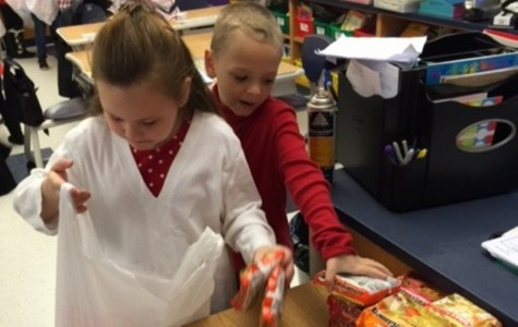Kids from Mrs. Longo's class pack backpacks for families during the holidays.