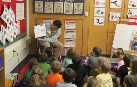 Senior Brennan McKendree reads to a group of elementary students last week as part of Read Across America Week.