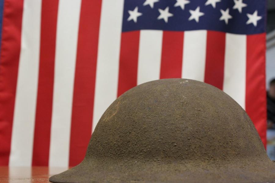 Mr. McNaul's War Helmet rests in front of the flag