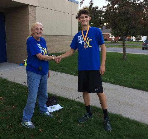 Junior Robert VanKirk is congratulated by Coach R after taking second at the ICC championship meet.
