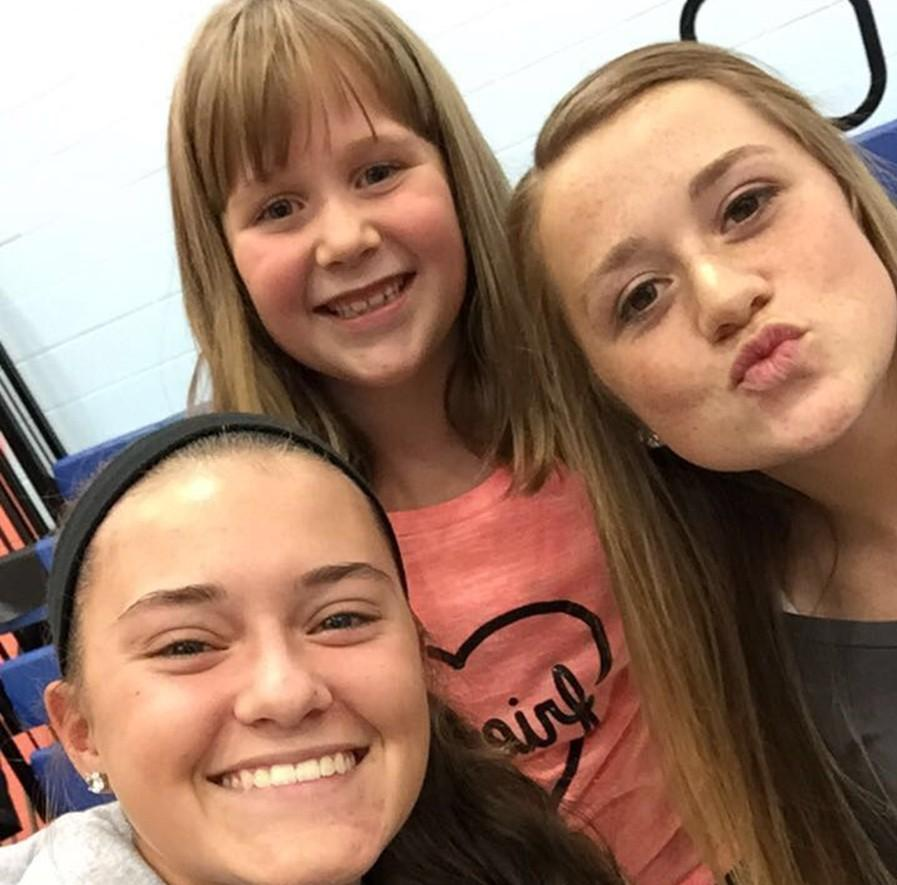 Volleyball seniors Abby Luensmann and Sophie Damiano took time for a selfie Wednesday with second grader Emma Taneyhill during the teams trip to Myers to build support for the program among the communitys young girls.