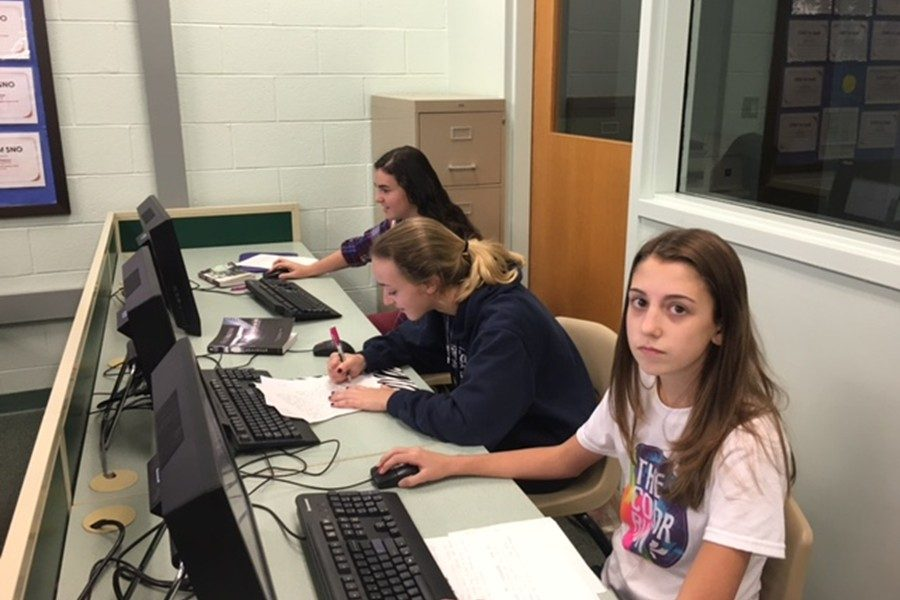 Emilee Leidig, Bennin Abbott and Emily Osborne work hard during eighth period. For them, the purpose was to finish an essay, but many students disagree on the purpose of education as a whole.