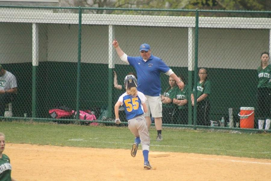 Ashtyn Payne rounding third with her father coaching along.