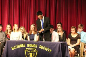 President Devon Zheng lights a candle at NHS inductions.