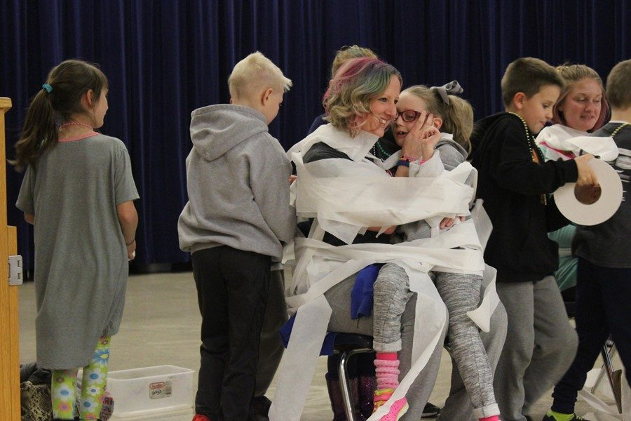 Second grade teacher Tara Naylor holds Maddie Shura as the two are toilet-papered as part of an award at the Myers Assembly to recognize International Childhood Cancer Awareness Week.
