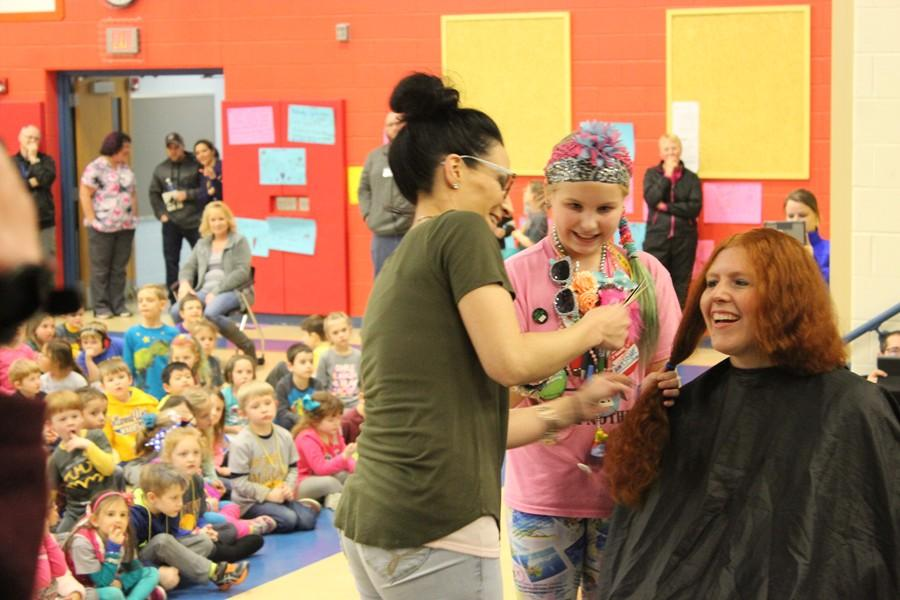 Myers teacher Tommie Murray had 12 inches of hair cut off for childhood cancer patients at a recent assembly.