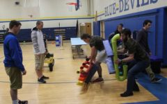 Ryan Moore and Jarryd Kissell help set up for STEM Night as Josh Swope watches on.