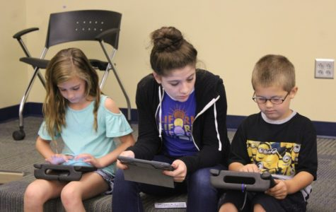 Isabella Barbosa works with second grade students on their reading project.