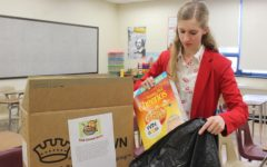 FCA member Cazen Cowfer collects cereal boxes from classrooms. The group is hoping to collect more than 1,300 boxes of cereal in its annual drive to benefit the St. Vincent DePaul Food Kitchen.