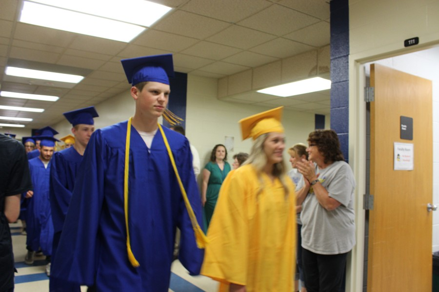 Trent Walker makes his way through the high school as faculty, students and staff applaud during the annual Senior Walk.