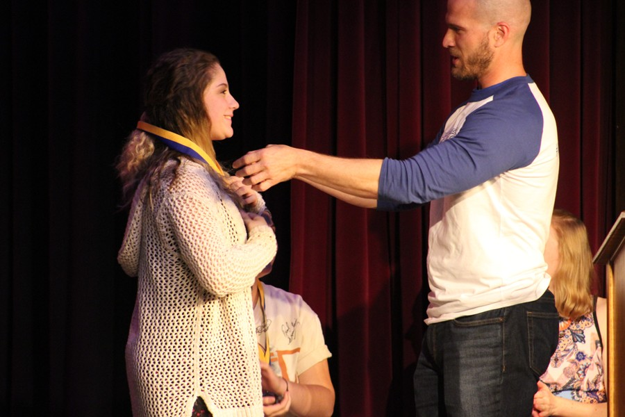 Isabella Barbosa receives her first place medal as the top overall slam poet at the 14th annual Poetry Slam.