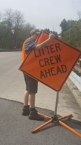 Brodee Wyland sets up a sign to alert traffic of the band's clean-up session.