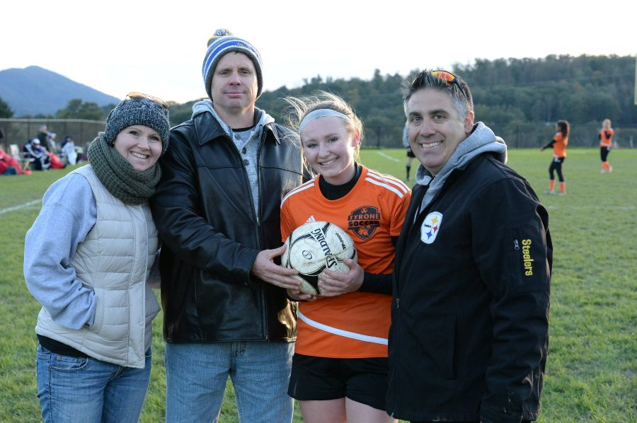 Riley D'Angelo celebrates her record-setting goal with her parents and coach.