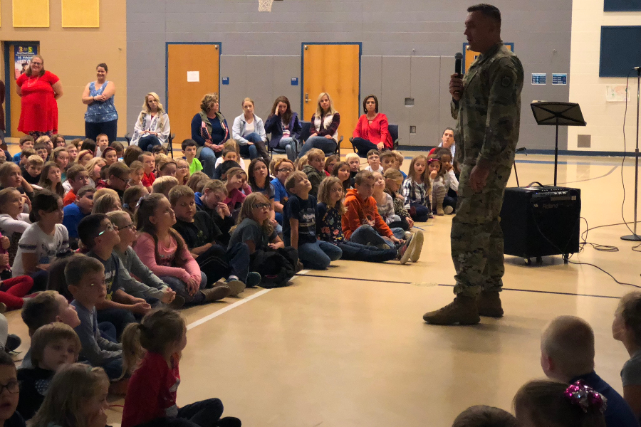 Sergeant Michael Smith , a local recruiter for the Army National Guard,  speaks to Myers students at their Stockings for Troop kickoff rally.
