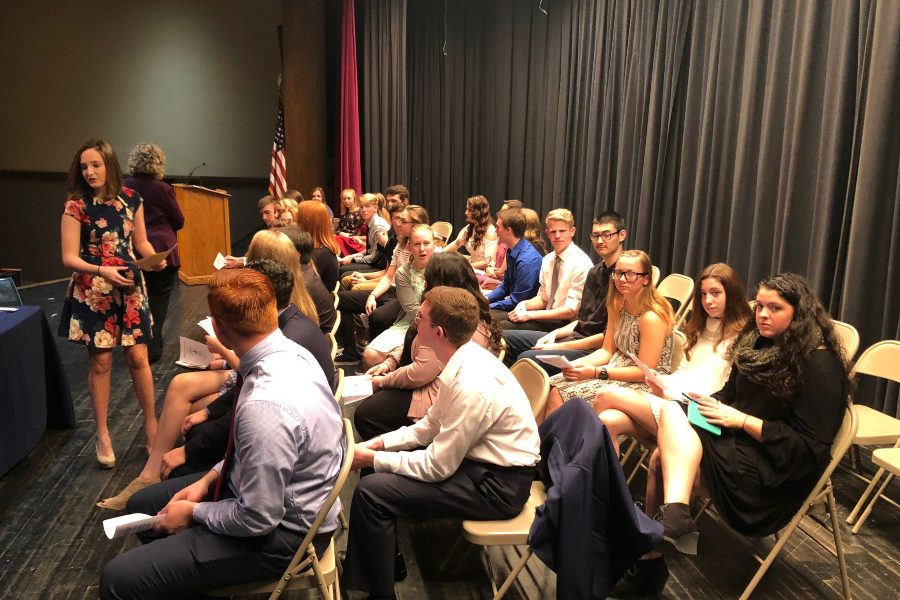 Students patiently wait on stage for the start of NHS inductions.