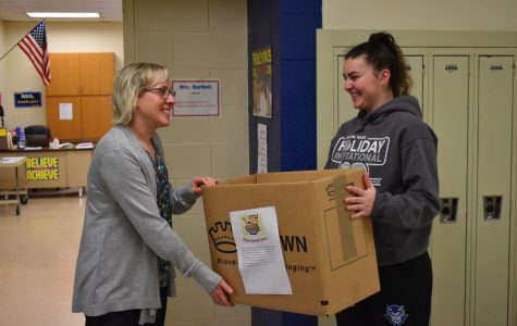 FCA member Emilie Leidig drops off a cereal drive collection box to Mrs. Bartlett's home room.