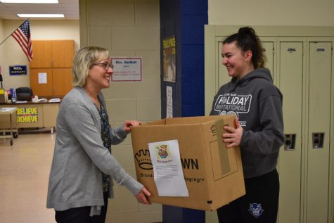 FCA member Emilie Leidig drops off a cereal drive collection box to Mrs. Bartlett