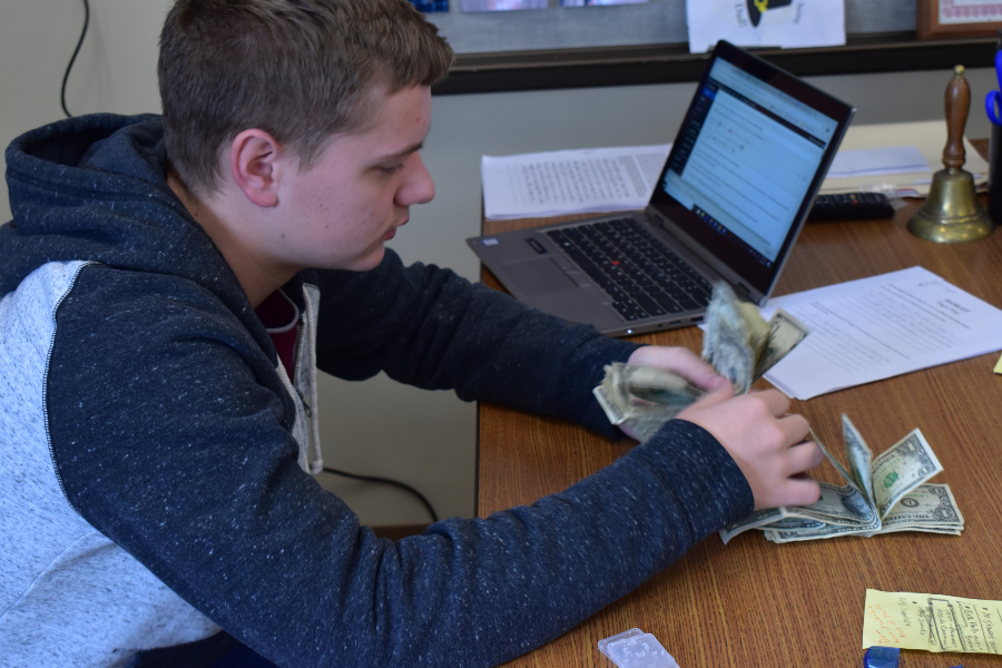Freshman Class Secretary Dawson Miller counts money raised for a new freshman scholarship.
