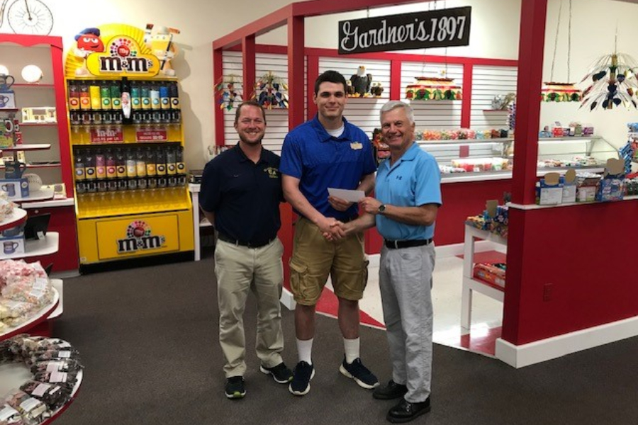 Caden Nagle receives a scholarship check from Gardners Candies president Sam Phillips with Coach Nick Lovrich.