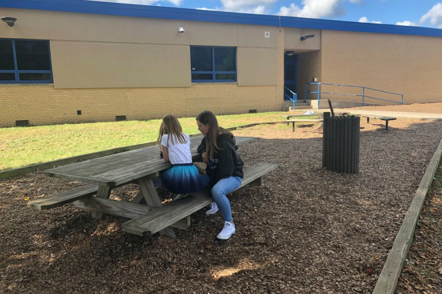 Ninth grader Olivia Kelly reads to a 2nd grader.