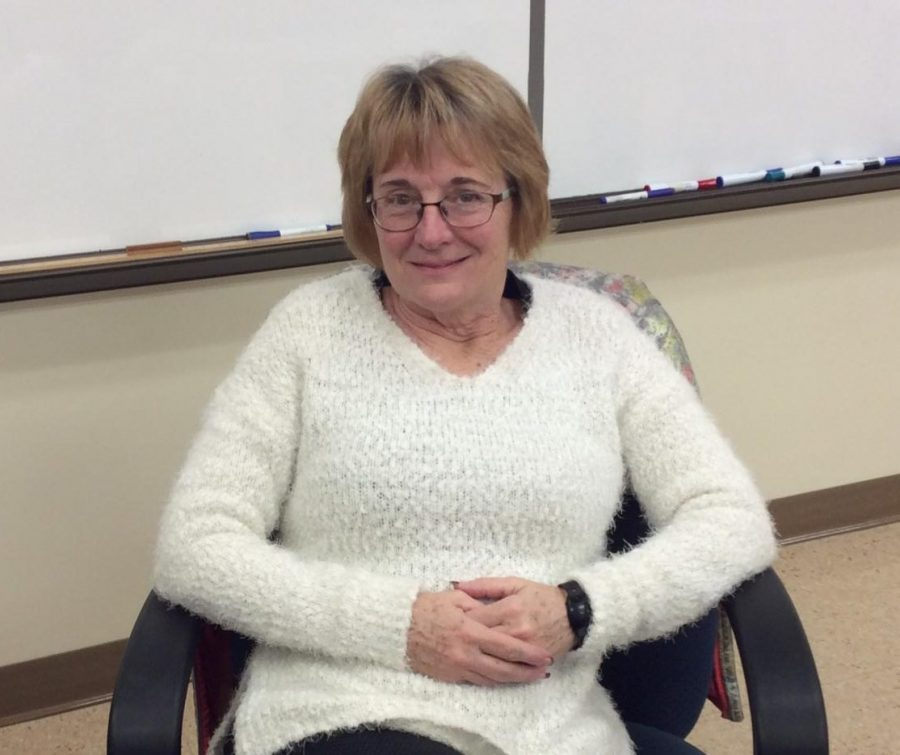 Mrs. Taylor sits at her desk in her middle school classroom.