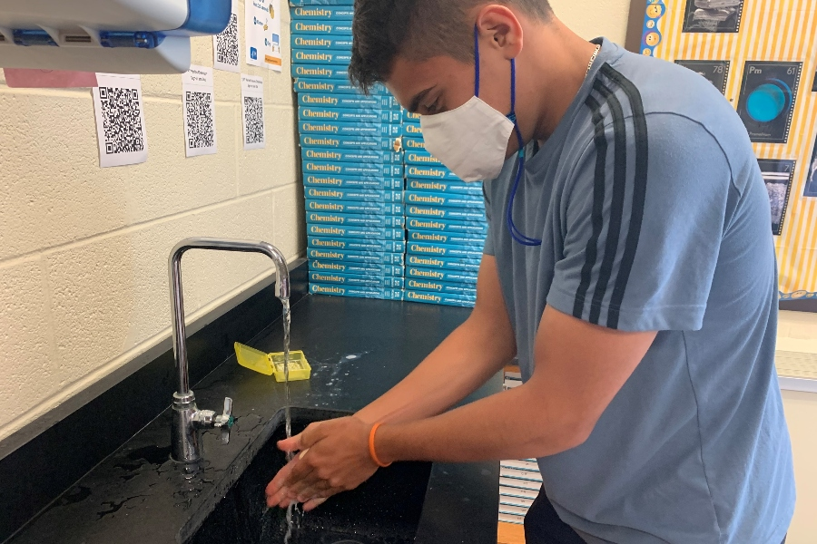 Andrew Tornatore takes time to wash his hands as he enters Ms. Clippard's room.