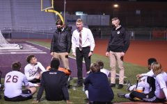 Soccer coach Alex Bartlett talks strategy with his team at halftime of the district 6 3A championship.