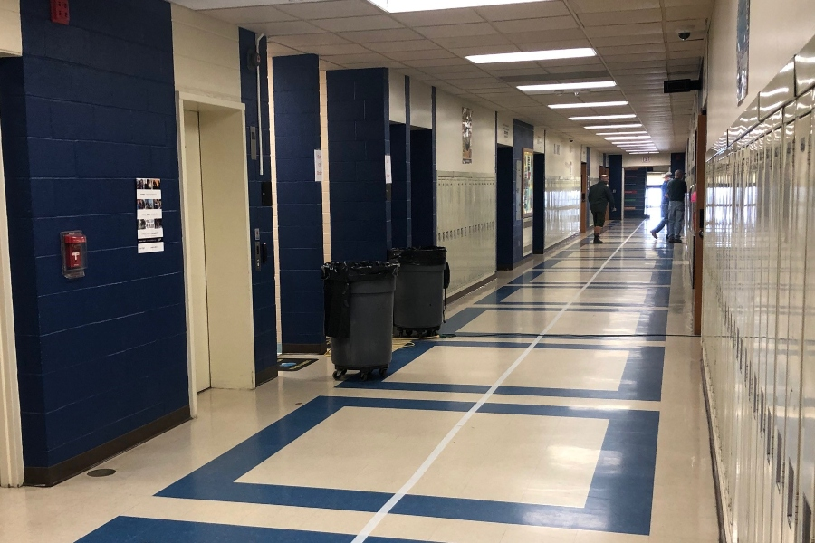 Custodians prepare high school bathrooms for cleanup after a sewage leak resulted in an early dismissal on Monday.
