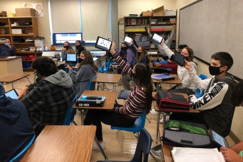 High school students back up their iPads in preparation for a possible move to virtual learning in the face of rising COVID numbers.