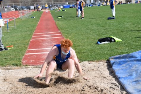 Nick Plank hits the pit in the long jump.