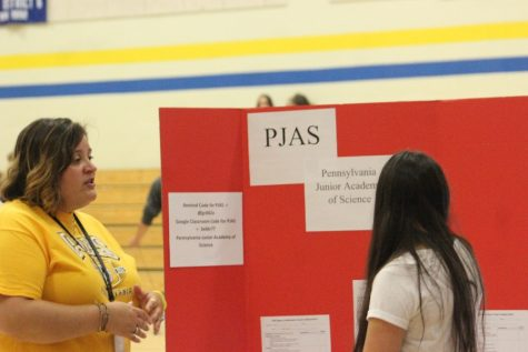 Ms. Shimel explains the benefits of PJAS to an interested student at the activity fair.