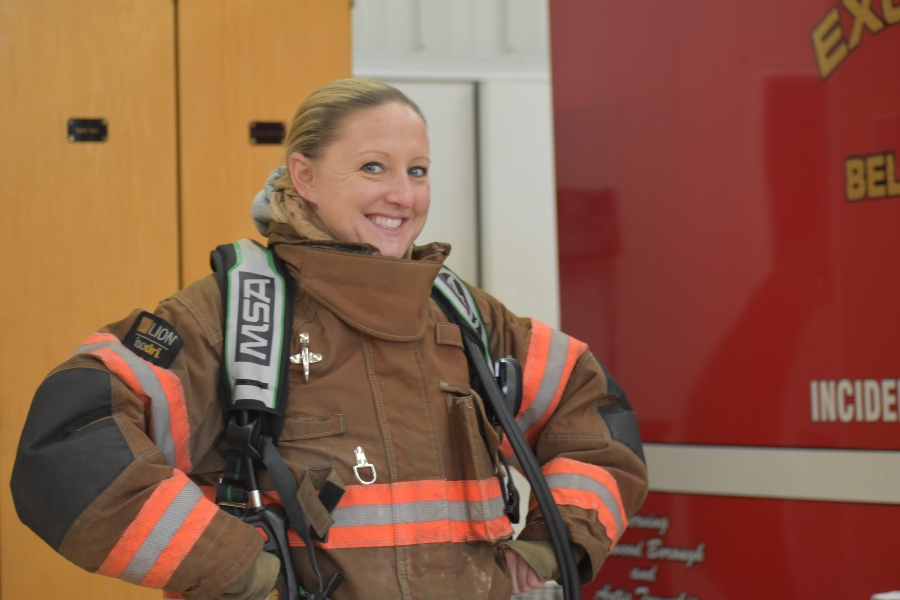 Second grade teacher Mrs. Naylor poses after trying on full fire fighting gear at Excelsior.
